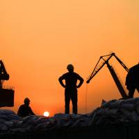Workers load imported goods at a port in Nantong, Jiangsu province, on Feb. 24.   REUTERS