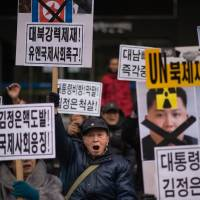 Anti-North Korea activists shout slogans and hold placards during a protest in Seoul on Monday. | AFP-JIJI