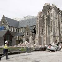A relief worker walks past the earthquake-damaged ChristChurch Cathedral, the best-known building in Christchurch, New Zealand, on Feb. 26, 2011. | AP