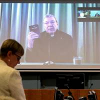 Senior Counsel Assisting Gail Furness stands in front of a screen displaying Australian Cardinal George Pell as he holds a Bible while appearing via video link from a hotel in Rome to testify at the Australia's Royal Commission into Institutional Response to Child Sexual Abuse in Sydney on Monday. Pell said on Sunday the Catholic Church had made 'enormous mistakes' as he became the highest-ranking Vatican official to testify on sexual abuse of children in the Church. | REUTERS / JEREMY PIPER-OCULI/HANDOUT VIA REUTERS