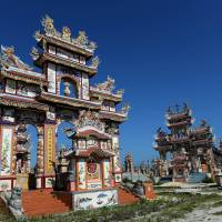 A Buddhist family tomb (left) and a Catholic family tomb stand at the cemetery in An Bang village, on the outskirts of Hue, Vietnam, on Dec. 2. | AFP-JIJI