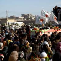 Syrian-Kurds attend the funeral procession of four Kurdish fighters in the northeastern Syrian city of Qamishli on Thursday. They died in the ongoing combat against Islamic State during an operation to take control of the town of Al-Shadadi, south of Hasakeh. | AFP-JIJI