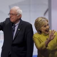 Democratic presidential candidates Bernie Sanders and Hillary Clinton arrive on the debating stage in Milwaukee on Thursday. | REUTERS
