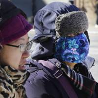 Women are bundled up as they walk in cold weather, Sunday in the Queens borough of New York. Bitter temperatures and biting winds had much of the northeastern United States bundling up this weekend. | AP