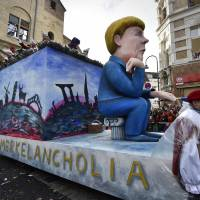A carnival float depicting Angela Merkel with a European flag that reads 'Merkelancholia' is seen during the traditional carnival parade in Cologne, western Germany, Monday. | AP