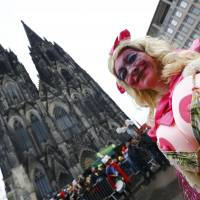 A carnival reveller takes part in the 'Rosenmontag' (Rose Monday) parade, the highlight of the annual carnival season in Cologne, Germany, Monday in front of the cathedral and main railway station. | REUTERS