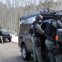 Jefferson County SWAT officers work at the scene where a man opened fire on sheriff's deputies before the officers returned fire, killing the man, outside Bailey, Colorado, Wednesday. Authorities say the man, who lost ownership of his home two years ago, opened fire on the officers trying to serve an eviction notice. | AP