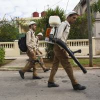 Government fumigators prepare to spray homes for mosquitos in Havana Monday. Cuban President Raul Castro announced Monday that he is dispatching soldiers to help keep the Zika virus out of Cuba, calling on the entire country to help kill the mosquito that carries the disease. | AP