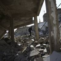 A man makes his way through rubble of damaged buildings in the Douma neighborhood of Damascus on Tuesday.   REUTERS