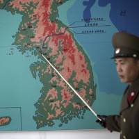 Korean People's Army Lt. Col. Nam Dong Ho points to a map showing the line that separates the two Koreas in Panmunjom at the Demilitarized Zone (DMZ) on Monday in Panmunjom, North Korea. Nam told The Associated Press that tensions have increased significantly along the Demilitarized Zone since North Korea conducted its nuclear test and rocket launch. He said he could not comment on operational details, but added: 'The reality is that it is touch and go.' | AP
