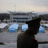 Korean People's Army Lt. Col. Nam Dong Ho is silhouetted against the truce village of Panmunjom at the Demilitarized Zone (DMZ) that separates the two Koreas on Monday. | AP
