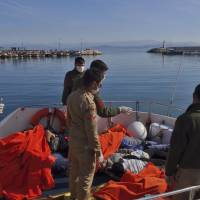 Members of Turkish forces look at the bodies of some of the migrants who drowned as they were trying to reach Greece, at a port in the coastal town of Dikili, near Izmir, Turkey, Monday,. Turkey's state-run news agency says dozens of migrants attempting to reach Greece have drowned after their boat sank off the Turkish coast. | AP