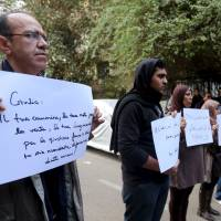 Activists hold placards that read, among others, 'Giulio, one of us and killed like us,' during a memorial for Giulio Regeni outside of the Italian Embassy in Cairo on Saturday. Dozens of people gathered at the embassy to mourn Italian student Giulio Regeni, whose body was found half naked at a roadside with what a senior Egyptian prosecutor has said were cigarette burns and other signs of torture. | REUTERS