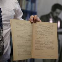 Roni Gross, curator of the Hebrew University's Albert Einstein Archive, displays original documents related to Albert Einstein's hypothesis of the existence of gravitational waves during a news conference in Jerusalem on Thursday. | REUTERS