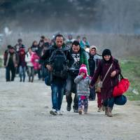 Migrants and refugees from Syria and Iraq cross the Greek-Macedonian border near the town of Gevgelija on Tuesday. | AFP-JIJI