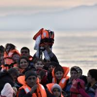 A man holds up a baby with a life jacket as refugees and migrants on a rubber boat arrive at the northern Greek island of Lesbos after crossing the Aegean sea from Turkey, in Mytilene, on Tuesday. | AFP-JIJI
