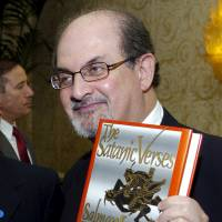 Author Salman Rushdie poses with his 1988 book 'The Satanic Verses' alongside fellow honoree Tashbih Sayyed before the American Jewish Conference's 30th Annual Dinner, 'Profiles in Courage: Voices of Muslim Reformers in the Modern World,' in Beverly Hills, California, in 2006. Iranian state-run media outlets have added $600,000 to a bounty for the killing of Rushdie imposed in 1989 over the publishing of 'The Satanic Verses.' | REUTERS