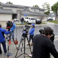 Members of the news media stand outside the home of Raheel Farook, brother of San Bernardino shooter Rizwan Farook, in Corona, California, Thursday. The FBI on Thursday searched the Southern California home. | REUTERS