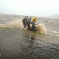 People are splashed by a wave whipped up by the encroaching cyclone Winston in Labasa, Fiji, on Saturday. | AP/FIJI TIMES/