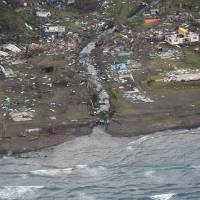 A handout photo taken Sunday and obtained Monday shows a damaged village on the main Fiji island of Viti Levu after the most powerful cyclone in Fiji's history battered the Pacific island nation. The category 5 super-storm lashed the popular tourist destination overnight on Saturday. | NEW ZEALAND DEFENSE FORCE / AFP-JIJI