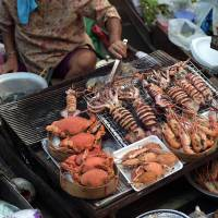 A Thai vendor roasts seafood on a boat moored along the Amphawa canal, a small tributary of the Mae Khlong River. | AFP-JIJI