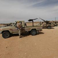 Libyan military vehicles are pictured at a checkpoint in Wadi Bey, west of the Islamic State-held city of Sirte, Tuesday. | REUTERS