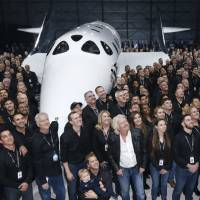 Richard Branson (white shirt) poses with staffers after unveiling the SpaceShipTwo, a six-passenger vehicle to carry people into space, on Friday in Mojave, California.   REUTERS