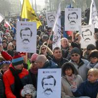 People hold pictures of former President Lech Walesa during a demonstration in Gdansk, Poland, Sunday. Poles protested the ruling Law and Justice (PiS) party and the government's recent accusations of Lech Walesa collaborating with the communist-era secret services. | AGENCJA GAZETA / RAFAL MALKO / REUTERS
