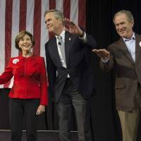 Former U.S. President George W. Bush waves with his wife, Laura, as he stands with his brother Jeb Bush during a campaign rally in Charleston, South Carolina, on Monday.   AFP-JIJI