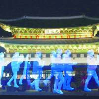 Holograms of protesters are shown on a screen during a rehearsal for a 'ghost protest' demanding the freedom of assembly in front of the 14th-century Gyeongbok Palace in Seoul on Wednesday. | AP