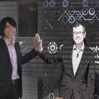 South Korean Lee Sedol, the world champion of the ancient Chinese board game go, poses with an image of Demis Hassabis, CEO of Google DeepMind, on a screen during a videoconference in Seoul on Monday. | AP