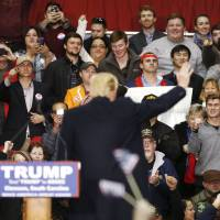 People cheer Republican presidential candidate Donald Trump (back to camera) at the end of his rally Wednesday at Clemson University in Pendleton, South Carolina. | REUTERS