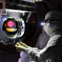 A Laser Interferometer Gravitational-wave Observatory (LIGO) technician performs a Large optic inspection in this undated photo released by Caltech/MIT/LIGO Laboratory on Tuesday. The twin detectors, a system of two identical detectors constructed to detect incredibly tiny vibrations from passing gravitational waves, are located in Livingston, Louisiana, and Hanford, Washington. Scientists said Thursday they have for the first time detected gravitational waves, ripples in space and time hypothesized by physicist Albert Einstein a century ago, in a landmark discovery that opens a new window for studying the cosmos. | REUTERS / CALTECH  /MIT / LIGO LABORATORY / HANDOUT VIA REUTERS