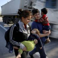 Stranded refugees carry their children along a national motorway toward the Greek-Macedonian border near the Greek town of Polykastro after ignoring warnings from Greek authorities that the border is shut, as hundreds of migrants set off on the country's main north-south motorway to the Idomeni border crossing Thursday. | REUTERS