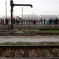 Refugees and migrants line up for food rations at the transit center for refugees near the northern Macedonian village of Tabanovce, while waiting for permission to cross the border into Serbia, Thursday. | AP