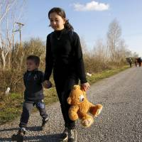 Stranded refugees walk a national motorway toward the Greek-Macedonian border near the Greek town of Polykastro Thursday. | REUTERS