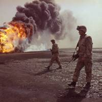 A U.S. Marine patrol walks across the charred oil landscape near a burning well during a perimeter security patrol near Kuwait City in March 1991.   AP