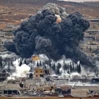 Smoke rises from the Syrian city of Kobani, following an airstrike by the U.S.-led coalition fighting the Islamic State group.   AP
