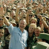 U.S. President George Bush poses with soldiers during a stop at an air base in Dhahran, Saudi Arabia, in November 1990.   AP