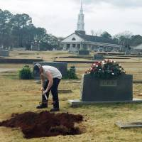 A man rakes soil over a grave in the Lee family cemetery plot Saturday in Monroeville, Alabama. | AP