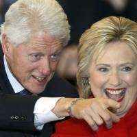 Democratic U.S. presidential candidate Hillary Clinton laughs as she celebrates with her husband, former President Bill Clinton, at a caucus rally in Des Moines, Iowa, on Monday. | REUTERS