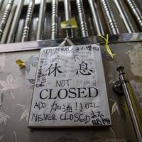 A 'closed' sign with words of support from visitors written on it is displayed outside the security gate of Causeway Bay Books in Hong Kong on Feb. 1. | AFP-JIJI