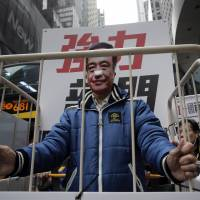 A protester in a cage wears a mask of missing publisher Lee Bo in Hong Kong on Jan. 10 during a demonstration against the disappearances of booksellers. | AP