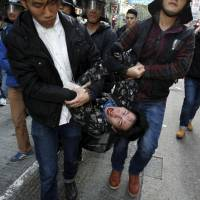 A protester shouts as he is arrested by plainclothes policemen after clashes in Hong Kong's Mong Kok district Tuesday. | REUTERS