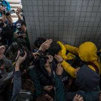 Members of the media gather as a supporter (top right in yellow jacket) helps escort a protester (top center covered with a black and yellow jacket), who is facing one count of taking part in a riot on Feb. 9 in the district of Mongkok, to a taxi after a court hearing in Hong Kong on Thursday. | AFP-JIJI