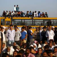 Demonstrators from the Jat community sit on top of a school bus as they block the Delhi-Haryana national highway during a protest at Sampla village in Haryana, India, Sunday. | REUTERS