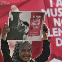 A Muslim takes part in a protest against Valentine's Day in Jakarta on Sunday. Activists urged Muslims to boycott the western holiday, calling it against Islamic teachings and warning that it could lead to forbidden sexual relations. | AP