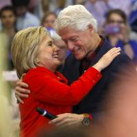 U.S. Democratic presidential candidate Hillary Clinton embraces husband former U.S. President Bill Clinton after being introduced onto the stage during a campaign rally at Washington High School in Cedar Rapids, Iowa, Saturday. | REUTERS
