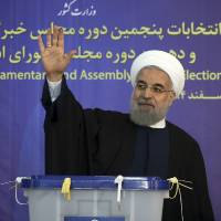 Iranian President Hassan Rouhani waves to reporters after casting his vote in Tehran on Friday. | AP