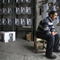 An Iranian man sits in a store next to posters of deputy parliament Speaker Mohammad Hassan Aboutorabi Fard, a candidate in the upcoming parliamentary elections, in Tehran on Monday. | AP